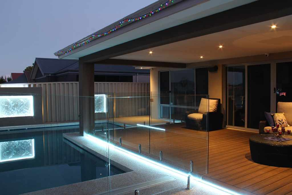 backyard with a pool, pot lights and led outdoor lighting